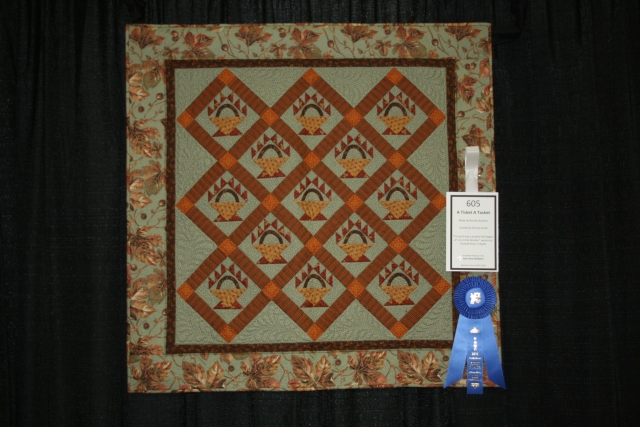 "10. Jo Morton's basket table topper started on 01/17/2011 and finished on 02/01/2011; ""a tisket a tasket"" quilted by Denise Green"