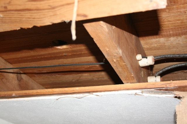 a new hole for the new toilet and you can see the old knob and tube wiring